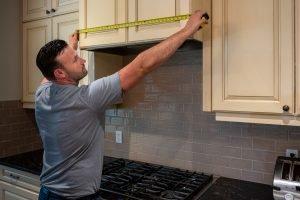 My Home Handyman measuring hood in kitchen