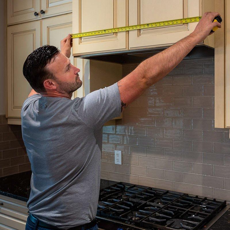 Handyman Measuring the Kitchen Cabinet